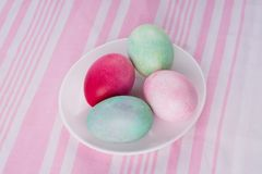 4 пестротканых покрашенных пасхального яйца на белых плите и stri Стоковые Фотографии RF