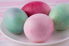4 пестротканых покрашенных пасхального яйца на белых плите и stri Стоковые Фото
