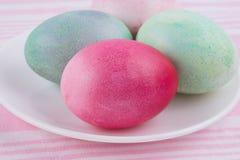 4 пестротканых покрашенных пасхального яйца на белых плите и stri Стоковое Изображение