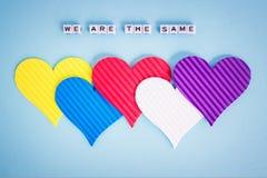 5 пестротканых сердец Валентайн и надпись мы эти же сделали из белых кубов alfphabet на пастельной голубой предпосылке стоковое изображение