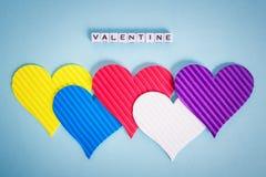 5 пестротканых сердец Валентайн и надпись Валентайн сделанное из белых кубов alfphabet на пастельной голубой предпосылке стоковые изображения rf