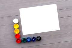 Пестрые краски и лист бумаги Стоковые Изображения