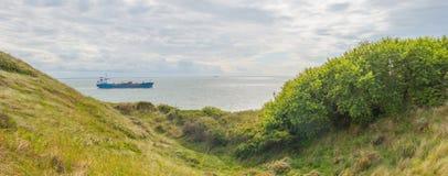 Песчанные дюны вдоль моря под голубым облачным небом Стоковое Изображение RF
