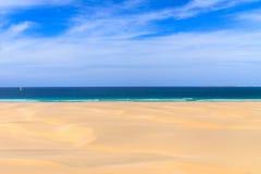 Песчанные дюны близко к океану с пасмурным голубым небом, Boavista, крышкой Стоковые Изображения RF