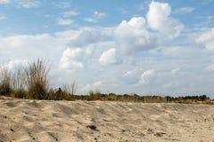 Песчанные дюны и трава против красивого неба с облаками Стоковая Фотография