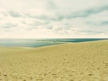 Песчанные дюны, море и облачное небо Стоковая Фотография