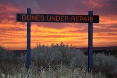 Песчанные дюны под знаком ремонта на заходе солнца Стоковое Изображение