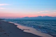 Песчаный пляж, голубое море и горы с облаками на предпосылке неба захода солнца Стоковые Изображения