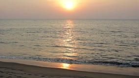 Песчаный пляж на предпосылке шлюпки в океане и солнечного пути под выравниваясь небом захода солнца видеоматериал