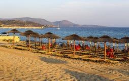 Песчаный пляж с sunbeds и зонтиками на вечере Пелопоннесе лета, Греции стоковая фотография