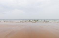 Песчаный пляж и волнистое море отделывают поверхность на побережье вэльса на пасмурном Стоковая Фотография RF