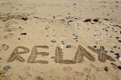 Песчаный пляж и предпосылка праздников с словом ОСЛАБЛЯЮТ Стоковые Фотографии RF
