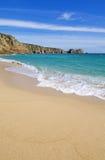 Песчаный пляж и Logan Porthcurno трясут в Корнуолле Англии Стоковые Изображения RF