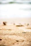 Песчаный пляж, камешки и море на предпосылке Стоковые Изображения
