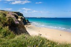 Песчаный пляж на ноге скалы в Корнуолле Стоковое Фото