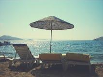 Песчаный пляж на солнечном после полудня, с парасолями и loungers солнца; ретро стиль Стоковые Фотографии RF