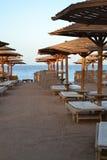 Песчаный пляж около моря с деревянным зонтиком Стоковые Фотографии RF
