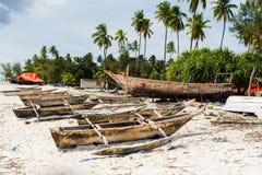 Песчаный пляж рыбацкого поселка с деревянными шлюпками в Занзибаре Стоковые Изображения