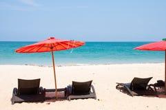Песчаный пляж с зонтиком и шезлонгом стоковые фотографии rf