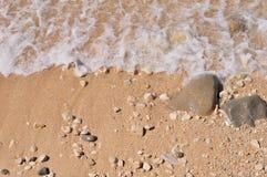 Песчаный пляж с камешками и волной стоковая фотография
