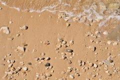 Песчаный пляж с камушками и волной стоковые фотографии rf