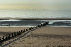 Песчаный пляж с оффшорными турбинами Стоковые Фотографии RF