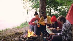 Петля Cinemagraph - группа в составе молодые человеки и женщины смотрят бумажные карты сидя вокруг огня в лесе с пить карта сток-видео