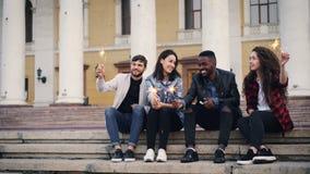 Петля Cinemagraph - счастливое молодые люди друзей в вскользь одеждах сидя на лестницах outdoors с гореть света Бенгалии акции видеоматериалы