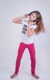 Петь девушки слушая и танцевать песню слушая на шлемофоне Стоковые Изображения