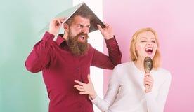 Петь ее страсть Дама поет использующ щетку волос как микрофон пока человек надоел прятать под компьтер-книжкой Лучший спойте на стоковые изображения rf
