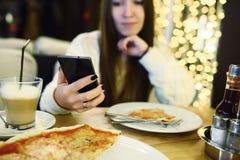 Печатать женщины пишет сообщение на умном телефоне в современном кафе Подрезанное изображение молодой милой девушки сидя на табли Стоковые Фото