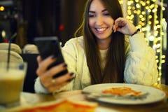 Печатать женщины пишет сообщение на умном телефоне в современном кафе Подрезанное изображение молодой милой девушки сидя на табли Стоковые Изображения