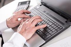 печатать на машинке компьтер-книжки компьютера бизнесмена Стоковые Фото