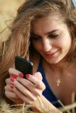 печатать на машинке мобильного телефона девушки Стоковые Фотографии RF