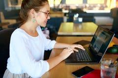 Печатать смешанной гонки женский на клавиатуре компьтер-книжки и использование сенсорной панели Диаграмма и диаграммы на экране А стоковая фотография rf