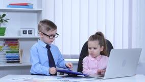 Печатают детей в компьтер-книжке и диаграммах взгляда голубой папки сток-видео