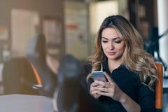 Печатая сообщение дела Уверенно молодая женщина в умной вскользь носке держа умный телефон и смотря его с улыбкой Стоковое Фото