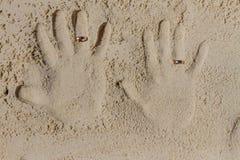 2 печати руки с обручальными кольцами на песке приставают к берегу, переплюнут Стоковые Фото