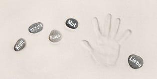 Печать руки в песке с камнями Немецкие слова для силы, вреда Стоковое Изображение RF