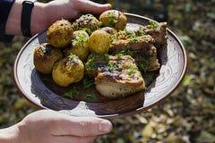Печеные картофели с нервюрами свинины на огне клали вне на плиту глины, украшенную с зелеными цветами Обедающий в природе стоковое изображение