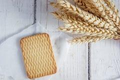 Печенье и ухо пшеницы на белом деревянном столе Стоковые Фото