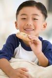 печенье мальчика есть живущих детенышей комнаты Стоковые Изображения