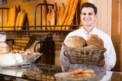 Печенье молодого мужского работника хлебопекарни предлагая Стоковое Изображение RF