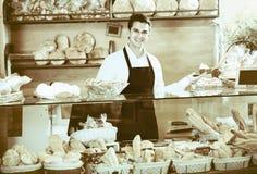 Печенье положительного мужского работника хлебопекарни предлагая Стоковая Фотография