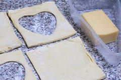 Печенье слойки для пиццы разделено в части, лежа на столешнице стоковое фото
