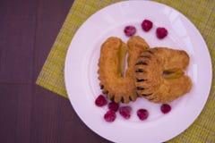 Печенье слойки при маковое семеня заполняя на белой плите с красным Ра стоковое изображение