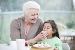 Печенье счастливой старшей женщины подавая к внучке дома Стоковые Фото