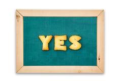 Печенья алфавита, слово ДА на предпосылке доски Стоковое фото RF