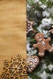 Печенья бумажные лист и пряник рождества на дереве покрытом снегом стоковые фото