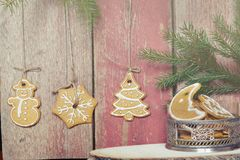 Печенья висят на веревочках от деревянной стены, около вазы с печеньями рождества Стоковые Фотографии RF